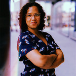 photo of abortion access advocate, Reneé Bracey Sherman, a Black woman with glasses and shoulder length curly hair, standing in front of a building wearing a patterned blue and red dress
