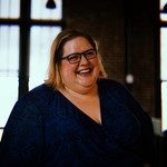 Rebecca Alexander, a plus-size white woman, smiles for the camera
