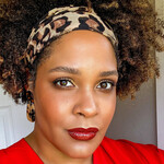 Ijeoma Oluo, a light-skinned Black woman with short brown hair, poses in a red shirt and a leopard-print headband