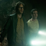 Bill Hader and James Ransone stand next to each other in a dark cave, looking afraid and holding a flashlight