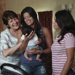 three Latina women stand in a semi-circle, smiling down an infant