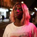 "Michaela Coel as Arabella Essiedu in ""I May Destroy You."" Michaela, a Black woman, wears a white t shirt and has a short pink bob. She stands in a street in the dark."