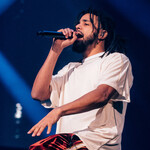 J. Cole, a lightskinned Black rapper with locs, sits onstage in a white t-shirt