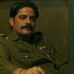 Jaideep Ahlawat plays Hathi Ram Chaudhary, an Indian man with short, black hair, sitting at a table in a green uniform
