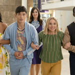 five people of all races walk hand in hand on The Good Place with excitement on their faces