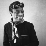 A photo of James Baldwin, a Black man. Baldwin smiles and looks to the right of the camera.