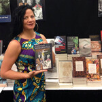 Jessica Krug, a white person with short, black hair, poses with a book in front of a table full of books