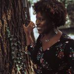Jessica Marie Johnson, an Afro Latinx woman with short, curly, black and brown hair, smiles next to a tree