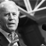 A black and white image of Joe Biden mid-speech behind a podium with a microphone