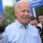 Joe Biden, an elderly white man with short, gray hair, stands at a rally