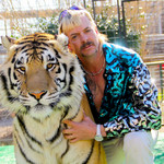 Joe Exotic, a white man with a blond mullet who's wearing a colorful top, poses next to a tiger