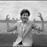 Judy Blume, a white author wearing a white suit, sits on a rooftop and smiles at the camera
