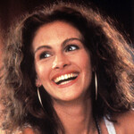 Julia Roberts, a white woman with a bright smile, brown hair, and gold hoops, plays Vivian in Pretty Woman