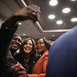 Kamala Harris, a light-skinned Black woman with short, brown hair, poses for a selfie with two Black women flanking her on each side