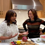Mindy Kaling, an Indian woman with long, black hair, stands beside Kamala Harris, a light-skinned Black woman with long, brown hair, in a kitchen