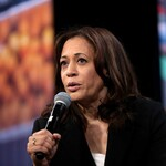 Kamala Harris, a Black woman with shoulder-length, straight, Black hair, speaks into a microphone while sitting down