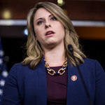Former Rep. Katie Hill speaks during a news conference on April 9, 2019 in Washington, DC. She is wearing a purple top with a navy blazer and a chunky gold necklace.