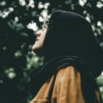 a Muslim woman wearing a black hijab and glasses is photographed in profile as she looks at the sky
