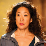 A closeup of a somber Sandra Oh with curly hair looking off screen