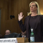 Kirstjen Nielsen stands and raises her right hand during her confirmation hearing