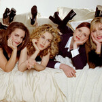 four thin, white women lay across a white-sheeted bed together for a promo for the Sex and the City