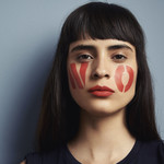 Zaira Gonzalez, a brownskinned Mexican model, poses with the word no written in red lipstick across her cheeks