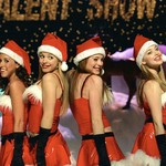 four white girls with brown and blonde hair wearing red Christmas outfits while standing on the stage