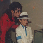 Michael Jackson, in red, with his hand on a young boy's shoulder in a grainy old photograph