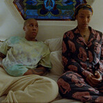 Lena Waithe as Denise and Naomi Ackie as Alicia, two queer Black women sitting on the bed together, in Master of None