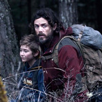 Casey Affleck and his character's daughter walk through a forest
