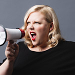 Lindy West, a white plus-size woman with shoulder-length blond hair and a black shirt, screams into a bullhorn
