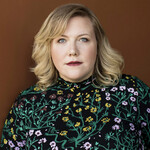 Lindy West, a fat white woman with blond hair, poses against a brown background in a flowered shirt