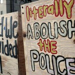 "A protester holds a sign that reads, ""Literally abolish the police."""
