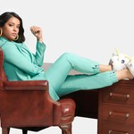 A woman of color in a sky blue blazer, pantsuit, and bunny slippers sits with her legs up on a desk.