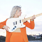 Liza Anne, who is white with bright blond hair, wears an orange suit and holds a guitar up against her chest on a beach.