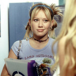 "Lizzie McGuire smirks while wearing her hair in two messy buns and a lavender baby tee that says ""camp outdoors"""
