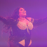 Lizzo, a plus-size Black woman musician, holds her arms open on stage as she performs in Australia