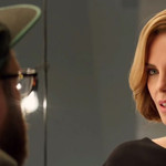 Charlize Theron in a conversation with Seth Rogen, who has his back to the camera