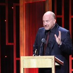 Louis CK standing on stage waving and smiling awkwardly