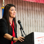 A photo of Lucy Flores. Flores, a Latina woman with dark hair, stands at a podium with a small smile.