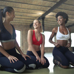 Three women wearing leggings and workout tops laughing together at a yoga studio