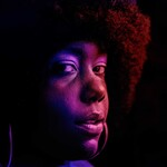 a Black woman with a black afro looks at the camera, covered under a red, orange, and deep purple filter