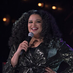 Michelle Buteau, who has light skin and curly hair parted down the middle, stands on stage in a glittery blazer during her comedy special.