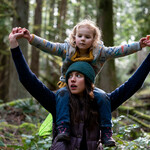 """Actress Margaret Qualley as Alex in """"Maid"""" holds a small child on her shoulders on a walk through the woods"""