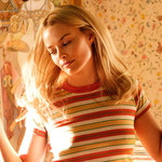 Margot Robbie snaps her fingers and dances, wearing a striped t-shirt