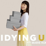 "Marie Kondo holding three gray boxes against a tan background with the title ""Tidying Up with Marie Kondo"""