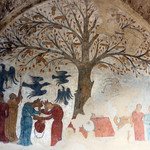 weathered painting of a large tree hung with penises and surrounded by women
