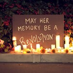a brown sign that says May Her Memory Be A Revolution in beige text is surrounded by candles