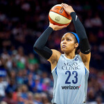 Maya Moore, a Black basketball player with a black ponytail, holds a basketball over her head as she shoots