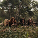 Four young women are laying in grass, surrounded by trees, learning how to shoot. The one with red hair and the one Asian woman are pointing sniper guns.